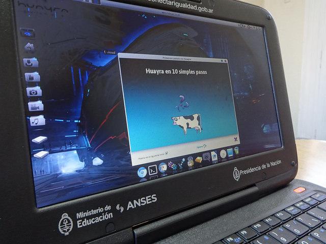 Una computadora portátil de las que se entregan a todo el alumnado de educación secundaria pública en Argentina. En la pantalla la imagen de una vaca volando, símbolo del sistema operativa Huayra, basado en el sistema libre Linus y creado localmente para el programa gubernamental Conectar Igualdad. Crédito: Fabiana Frayssinet/IPS