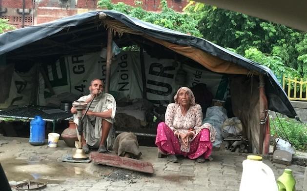 """Una pareja de personas mayores sentada frente a su """"casa"""", una estructura hecha con bolsas de plástico y materiales de desechos. Crédito: Neeta Lal/IPS"""