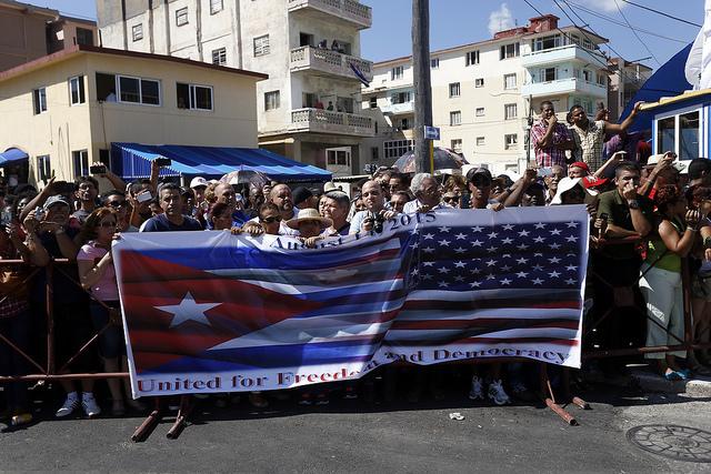 """Cientos de personas asistieron, detrás de una pancarta con las banderas de Cuba y Estados Unidos, donde se leía en inglés """"Unidos por la libertad y la democracia"""", a la ceremonia de reapertura formal de la embajada de Washington ante La Habana. Crédito: Jorge Luis Baños/IPS"""