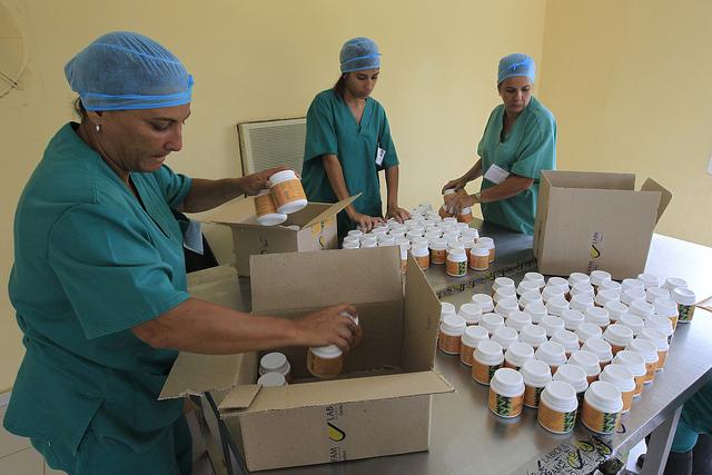 Tres mujeres trabajan en el envasado y etiquetado de píldoras de espirulina, en la planta de producción de espirulina, de la empresa estatal Genix-Labiofam, en la localidad de Zaragoza, en Cuba. Crédito: Jorge Luis Baños/IPS