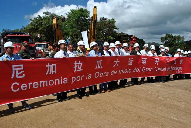 Ejecutivos de la empresa china HKDN-Group detrás de una gran pancarta, el 22 de diciembre de 2014, en la localidad de Brito Rivas, en la costa del océano Pacífico, en el acto de comienzo formal de la gigantesca obra del Gran Canal de Nicaragua, que partirá en dos el país. Crédito: Mario Moncada/IPS