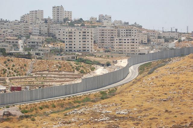 El muro de separación se extiende entre el asentamiento israelí de Pisgat Zeev y un campamento de refugiados palestinos. Crédito: Jillian Kestler-D'Amours/IPS