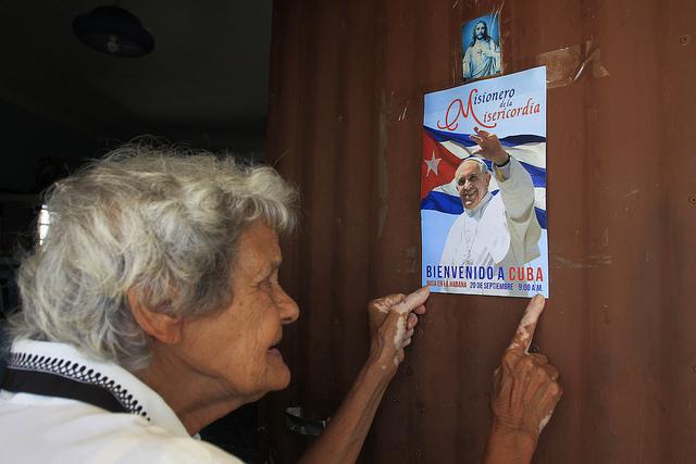 Pastora Rodríguez, de 85 años, coloca en la puerta de su humilde vivienda un cartel de bienvenida al papa Francisco, en el asentamiento rural del Consejo Popular Pablo Noriega, a 50 kilómetros al sur de La Habana, en Cuba. Crédito: Jorge Luis Baños/IPS