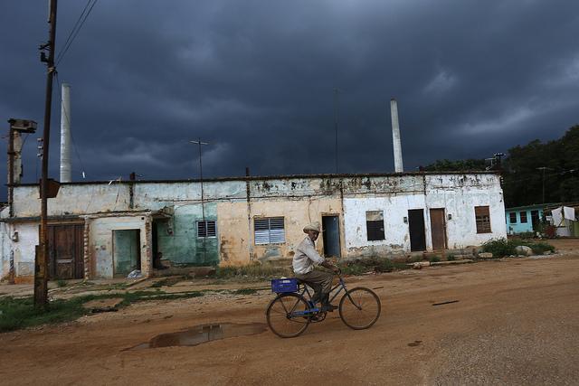 Un hombre transita en bicicleta por áreas deterioradas del antiguo Central Azucarero Pablo Noriega,   en el pueblo de Consejo Popular Pablo Noriega, a 50 kilómetros al sur de La Habana, en Cuba. Crédito: Jorge Luis Baños/IPS