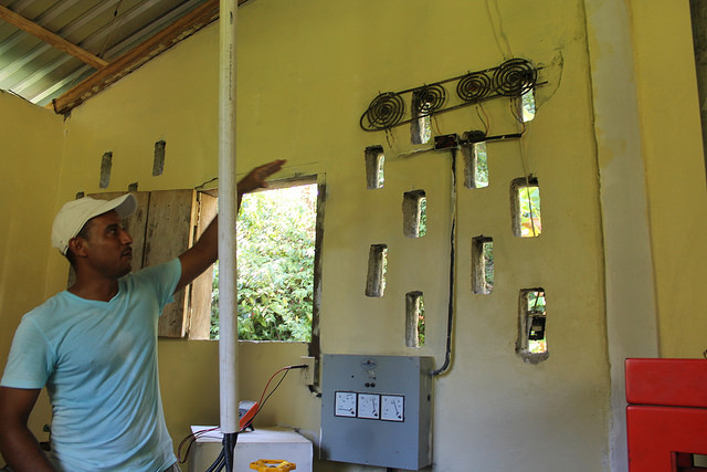 Edgardo Padilla, quien administra el uso de la pequeña central hidroeléctrica, explica cómo opera el proceso y las reglas que han establecido para hacer un uso racional del consumo y distribución de la electricidad en Plan Grande, una comunidad de pescadores de la costa atlántica de Honduras. Crédito: Thelma Mejía/IPS