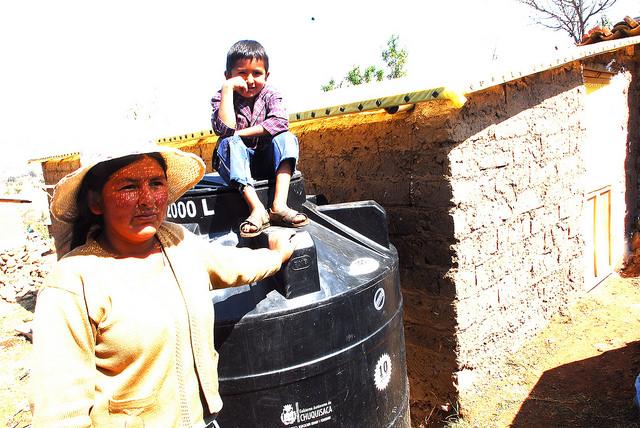 Una de las horticultoras periurbanas de las afueras de Sucre junto a su hijo, subido orgulloso en el tanque de agua, donado por la gobernación de Chuquisaca y con capacidad para 2.000 litros, donde almacena el agua de lluvia para luego filtrarla mediante goteo a las verduras orgánicas que ella cultiva. Crédito: Franz Chávez/IPS