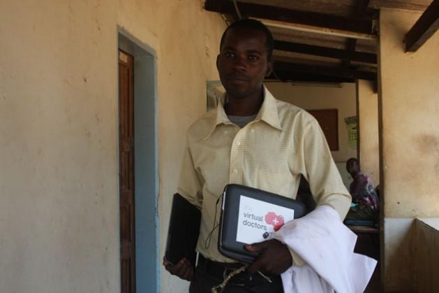 El paramédico Kennedy Mulenga, de la clínica de Ngwerere, carga una vieja netbook de Virtual Doctors en su mano izquierda y una nueva tableta, en la derecha. Crédito: James Jeffrey/IPS.