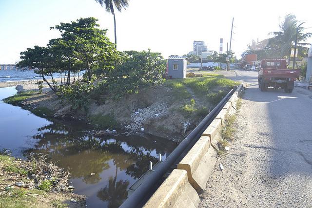 Desembocadura del Ñagá, un río de aguas oscuras y cauce estrecho por los vertidos industriales y la pérdida de sus manglares, en la costera ciudad de Bajos de Haina, en República Dominicana. Crédito: Dionny Matos/IPS