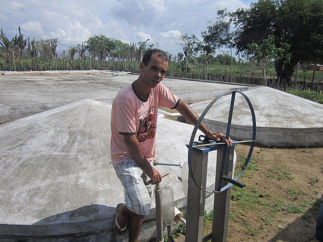 Abel Manto en la terraza con cisternas cerradas para recoger el agua de lluvia e irrigar sus huertos, en el estado de Bahia, en Brasil. El verde de la finca de este campesino e inventor contrasta con la aridez de la región, mientras que el sistema de cerramiento de sus cisternas impide que los mosquitos infecciosos aniden en el líquido. Crédito: Mario Osava/IPS
