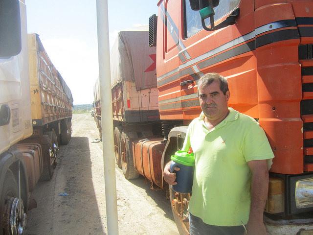 """Martin Echauri coincide con otros camioneros que transportan la soja al Complejo Agroindustrial Angostura SA (Caiasa), en que esta planta procesadora de la oleaginosa es """"una bendición"""", por la rapidez del proceso de descarga de los 500 vehículos de gran tonelaje que en promedio llegan cada día a sus instalaciones, en Angostura, en el parque industrial de Villeta, en Paraguay. Echauri, distrae la espera compartiendo con otros camioneros la infusión de hierba mate, muy popular en los países del Cono Sur Americano, que mantiene en un termo especial. Crédito: Mario Osava/IPS"""