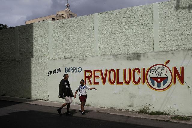 """Dos personas transitan al lado de una cartel en el que  puede leerse la frase """"En cada barrio revolución"""", en una calle de Centro Habana, en la capital de Cuba, que resalta la importancia de cada asentamiento para el poder político del país. Crédito: Jorge Luis Baños/IPS"""