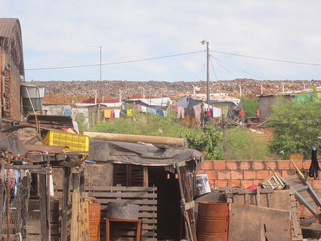 Abajo, casas destruidas por las inundaciones en Bañado Sur, uno de los barrios de población mayoritariamente pobre de las riberas del río Paraguay en Asunción. En el centro, las casuchas fabricadas algo más arriba por quienes se negaron a dejar el área, y al fondo el vertedero el basural que atrajo a muchos pobladores hacia este humedal con recurrentes inundaciones. Crédito: Mario Osava/IPS