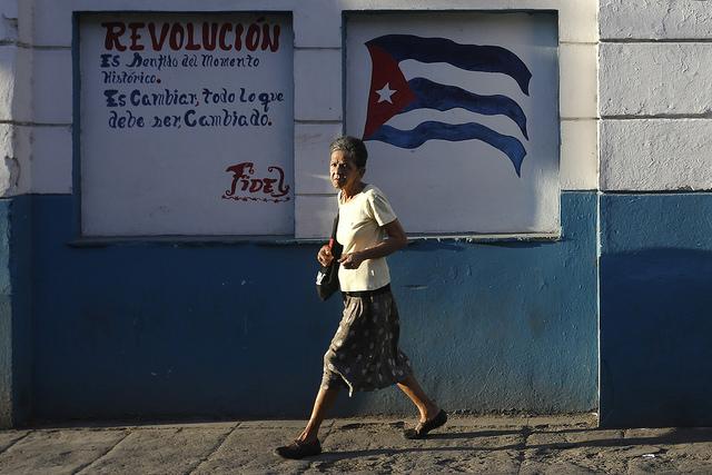 """Una mujer camina por una calle céntrica de La Habana, delante de un grafiti en el que se observa la bandera de Cuba junto a la frase del líder histórico Fidel Castro: """"Revolución es sentido del momento histórico. Es cambiar todo lo que debe ser cambiado"""", que funciona como reclamo para el VII Congreso del Partido Comunista de Cuba. Crédito: Jorge Luis Baños/IPS"""