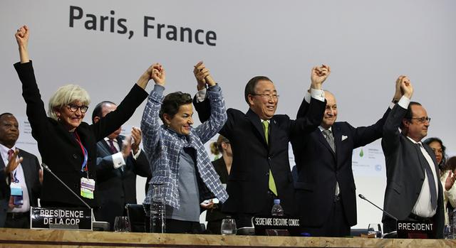 En la tarima del plenario de la COP21, el secretario general de la Organización de las Naciones Unidas, Ban Ki-moon, en el centro, junto con otros dignatarios celebran el 12 de diciembre el alcance del histórico Acuerdo de París sobre el cambio climático, que ahora se firma en Nueva York. Crédito: Naciones Unidas