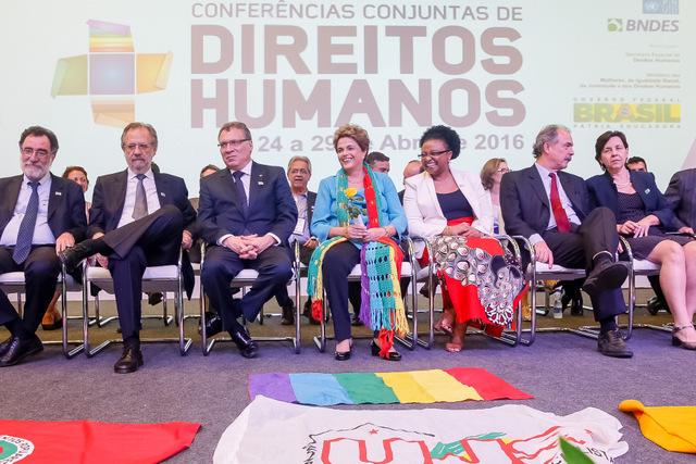 La presidenta Dilma Rousseff, sentada en el centro, con una flor en la mano que le acaba de ser entregada, durante la apertura de la Conferencia Nacional de Derechos Humanos, inaugurada el 27 de abril en Brasilia. En los actos de la mandataria de estos días se repiten los gestos de cariño con olor a despedida hacia la mandataria. Crédito: Roberto Stuckert Filho/PR