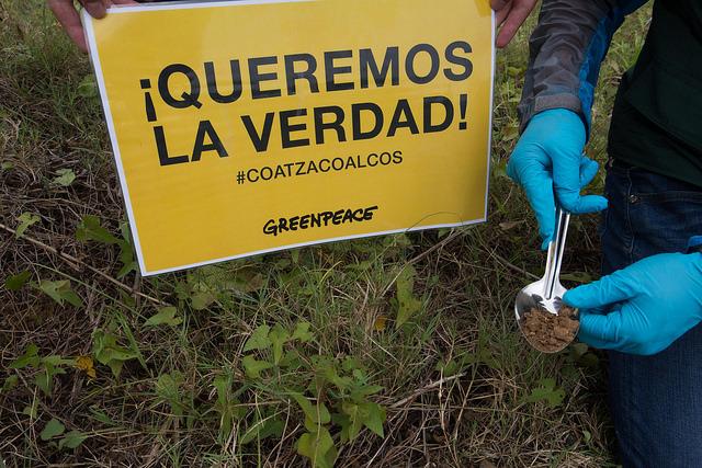 """""""¡Queremos la verdad!"""" sobre lo sucedido en el estallido de una planta productora de policloruro de vinilo (PVC), en un complejo petroquímico situado en la ciudad de Coatzacoalcos, en el sudeste de México, dice el cartel de Greenpeace, mientras un técnico toma una muestra del suelo tras la explosión. Crédito: Greenpeace México"""
