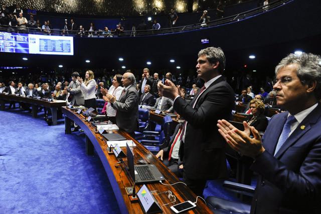 Un grupo de fatigados senadores aplaude al final de la maratónica sesión que decidió la separación inmediata de la presidenta Dilma Rousseff de sus funciones, mientras el Senado, convertido en tribunal, establece en un juicio político si hay razones para su casi segura destitución. Crédito: Marcos Oliveira/Agência Senado