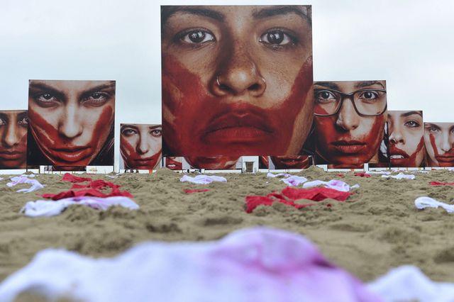 La organización Río Paz llenó la arena de la playa de Copacabana, en la ciudad de Río de Janeiro, de ropa interior femenina del color de la sangre o ensangrentada y de gigantografías de mujeres de rostros también ensangrentados, representando a la población femenina asesinada en Brasil. Crédito: Tânia Rêgo/Agência Brasil