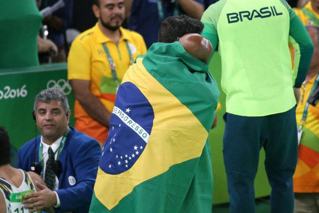 El gimnasta Diego Hypolito, completamente tapado por la bandera de Brasil, abrazado por su entrenador, tras ganar la medalla de plata en la competición de suelo, se convirtió en otro nuevo héroe olímpico del país, al ganar esa presea ya con 30 años, tras fracasar en los Juegos de 2008 y 2012. Crédito: Roberto Castro/ Brasil2016