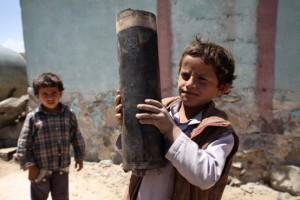 Un niño sostiene una gran parte de un dispositivo de artillería que cayó sobre Al Mahjar, un barrio de Saná, Yemen. Crédito: Mohamed Hamoud/UNICEF.