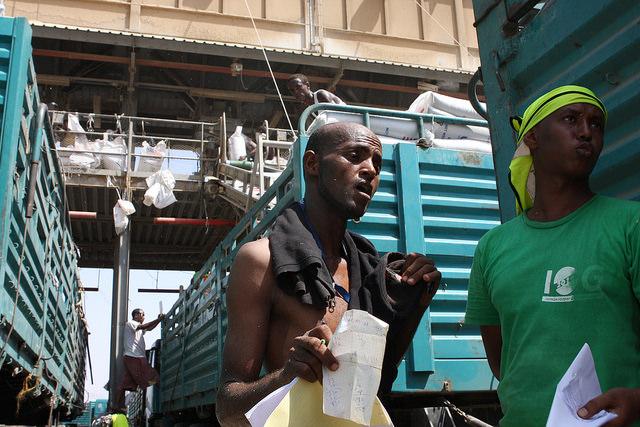 Los trabajadores portuarios aprovechan al máximo cualquier sombra que puedan encontrar entre los camiones cargados con asistencia alimentaria para Etiopía, agobiada por la sequía. Crédito: James Jeffrey/IPS.