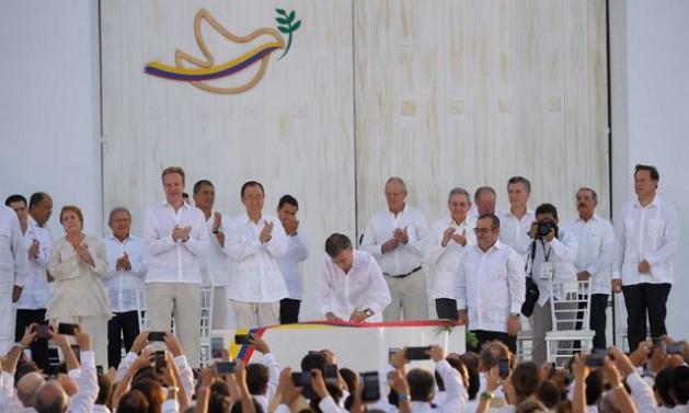 El presidente de Colombia, Juan Manuel Santos, firma el Acuerdo Final de paz, ante la mirada del jefe de las FARC, Rodrigo Londoño, mandatarios latinoamericanos y otras autoridades, en un acto al aire libre en la ciudad de Cartagena de Indias. Crédito: Presidencia de Colombia