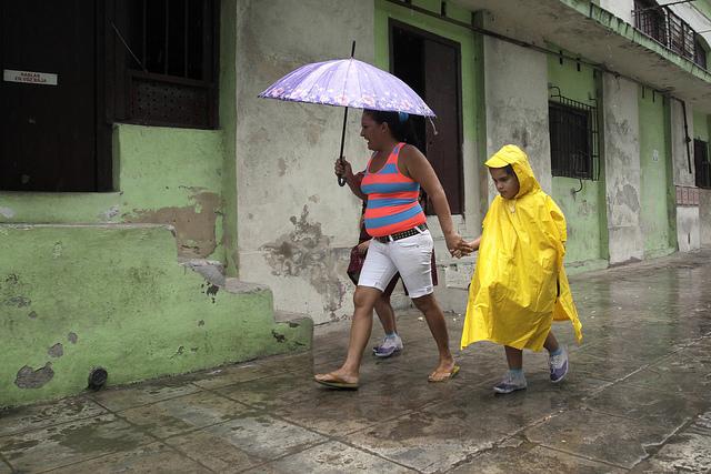 Una madre camina con sus dos pequeñas hijas que ha ido a buscar a la escuela, por una calle de La Habana. Cuando estas niñas cubanas sean adultas, tendrán 52 por ciento de probabilidad de ser las jefas de su hogar, según proyecciones oficiales. Crédito: Jorge Luis Baños/IPS