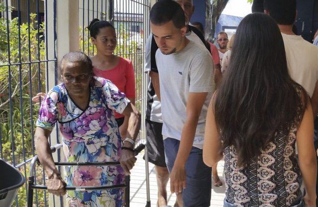 Una mujer con dificultades de movilidad, cuando acudía a votar, ayudada por su nieta, en las elecciones municipales de Brasil, el 2 de octubre, en la ciudad de Recife. El voto femenino es determinante en el país, pero la presencia de mujeres en cargos de elección resulta muy baja. Crédito: Sumaia Villela/Agência Brasil