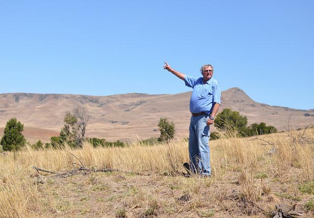 El agricultor y presidente del Ambiente Protegido de Mabola, Oubaas Malan, señala su hacienda desde el sitio donde se instalaría la mina. Crédito: Mark Olalde/IPS.