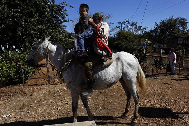 Un padre sube al caballo a su hijo, tras recogerlo de la escuela en una comunidad rural de la central provincia de Villa Clara, en Cuba. Las normas para estimular la maternidad en el país incluyen poco a los padres, a juicio de los especialistas. Crédito: Jorge Luis Baños/IPS