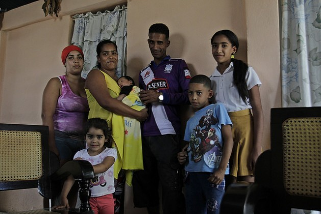 La maestra Yudith Osorio, de 37 años, sostiene en sus brazos a su cuarto hijo, una niña, mientras posa con su familia, que ya incluye una nieta, en su hogar en Palenque, cabecera del municipio rural de Yateras, en la oriental provincia cubana de Guantánamo. Crédito: Jorge Luis Baños/IPS
