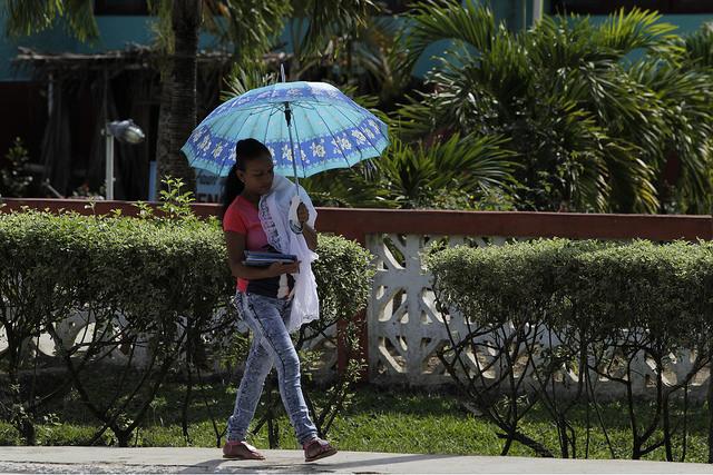 Una joven madre camina, cargando su bebe y unos cuadernos escolares por una calle de Palenque, capital del municipio de Yateras, donde la tasa de fecundidad es muy superior al promedio de Cuba. Crédito: Jorge Luis Baños/IPS