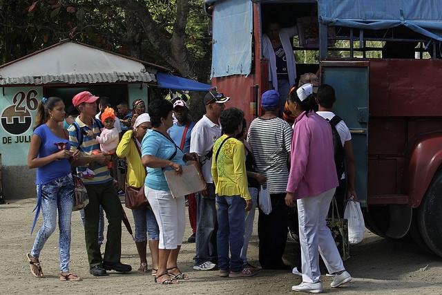 Una pareja con su pequeña hija entre otros pasajeros que se aprestan a abordar un camión habilitado para el transporte público por un grupo de chóferes privados, en Palenque, en el municipio rural de Yateras, en el oriente de Cuba. Crédito: Jorge Luis Baños/IPS