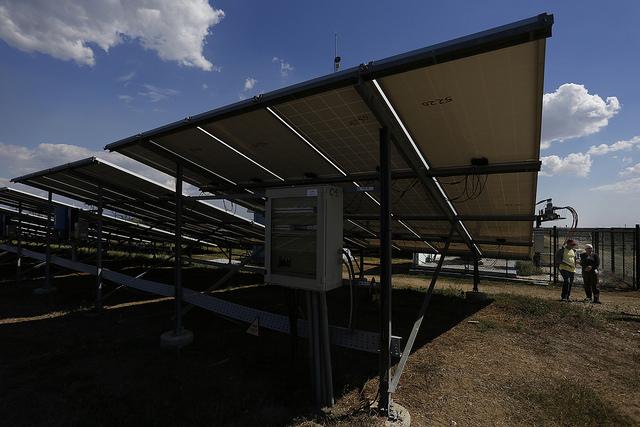 Igori Suárez (izquierda) y Migdalia Faer, al fondo, junto a una de las filas de paneles del Parque Solar Fotovoltaico Santa Teresa, en el barrio de Los Güiros, en la periferia sur de la ciudad de Guantánamo, capital de la provincia del mismo nombre, en el oriente de Cuba. Jorge Luis Baños/IPS