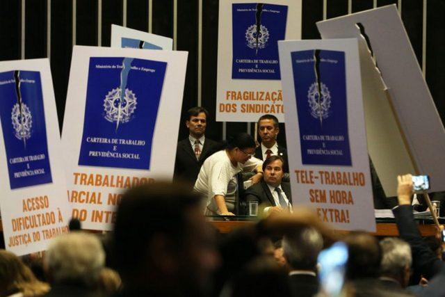 Diputados de oposición protestan con pancartas en la sesión donde su cámara aprobó el proyecto de ley que altera la legislación laboral brasileña, priorizando negociaciones directas entre empleados y patrones, dificultando el acceso a la Justicia del Trabajo y las actividades sindicales. Crédito: Antonio Cruz/Agência Brasil