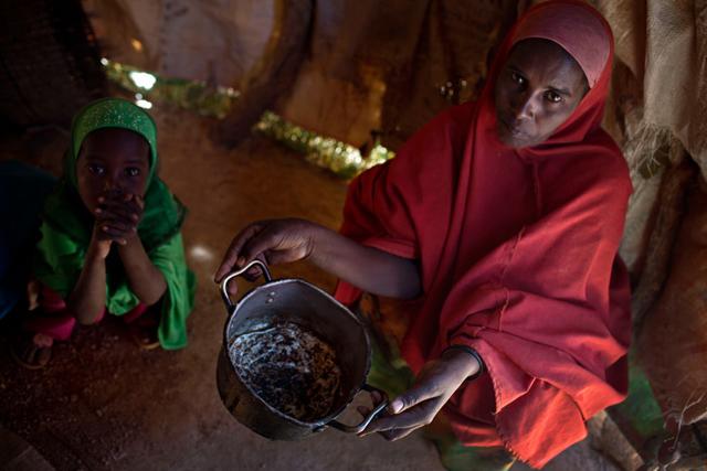 Una madre sostiene una olla vacía dentro de su casa improvisada en un asentamiento cerca de la ciudad de Ainabo, Somalia, en marzo de 2017. Foto: Kate Holt / Unicef