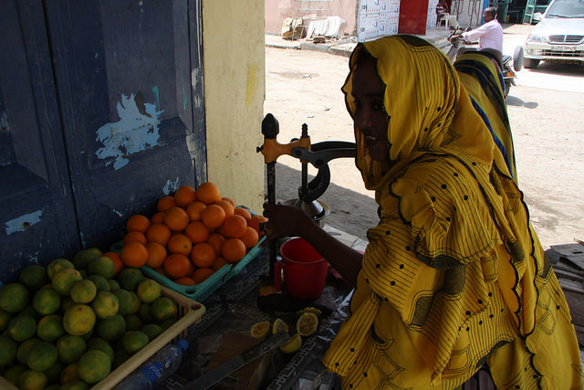 Una mujer vende jugo fresco en la calle para saciar la sed de los transeúntes bajo el sol abrasador de Yibuti. Crédito: James Jeffrey/IPS.