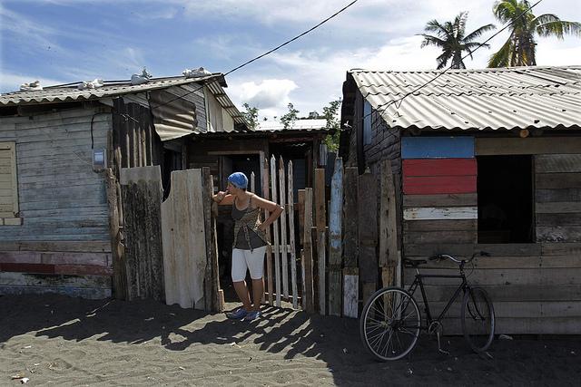 Una mujer ante la entrada de su vivienda, construida sobre la arena del tibaracón de la desembocadura del río Macaguaní, en el municipio de Baracoa, en el oriente de Cuba. Los pobladores de su asentamiento deberán ser reubicados por la vulnerabilidad climática del lugar. Crédito: Jorge Luis Baños/IPS