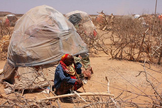 Un adulto mayor en cuclillas afuera de su refugio en un campamento para personas desplazadas en la zona de Gode, en la región somalí de Etiopía. Crédito: James Jeffrey/IPS.