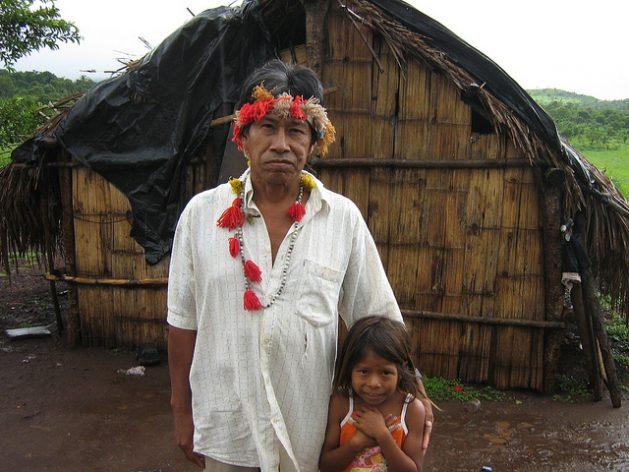El guaraní Hamilton Lopes y su hija, frente a su choza, donde su familia vive precariamente en tierras sin demarcar y con amenazas de expulsión, en la frontera de Brasil con Paraguay. Allí los terratenientes se apropiaron de sus tierras, provocando el mayor número de asesinatos y suicidios de indígenas. Crédito: Mario Osava/IPS