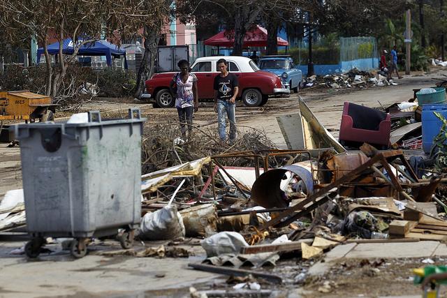 Dos personas caminan el miércoles 13 de septiembre en medio de los escombros y objetos esparcidos por una calle del barrio del Vedado tras el paso del huracán Irma por la capital de Cuba. Crédito: Jorge Luis Baños/IPS