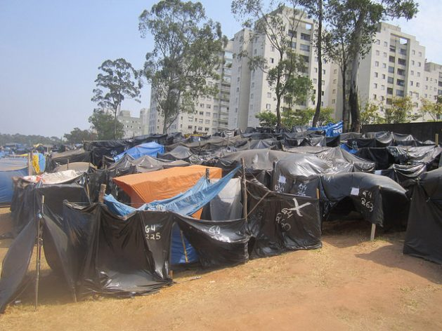 Tiendas precarias de plástico negro se amontonan a lo largo de un kilómetro, en un predio abandonado de 60.000 metros cuadrados, ocupado por 7.000 familias en busca de una vivienda asequible, en un campamento rodeado de edificios de clase media, en São Bernardo do Campo, en el sur de Brasil. Crédito: Mario Osava/IPS