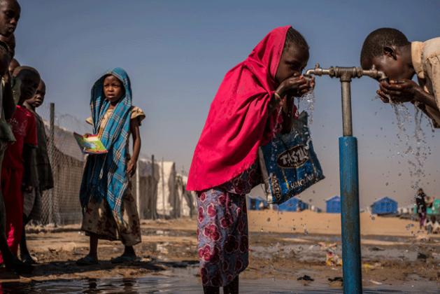 Niños beben agua de un grifo durante un receso en la escuela primaria que recibe asistencia de Unicef en el campamento para personas desplazadas en Bukasi, en Maiduguri, en el estado de Borno, Nigeria. Crédito: Gilbertson/Unicef.