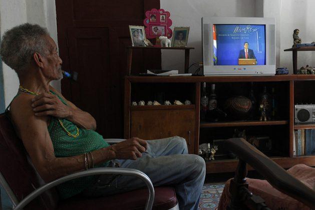 Fernando Machado, de 77años, observa al canciller cubano Bruno Rodríguez durante la transmisión televisiva de su conferencia de prensa el 3 de octubre, en que calificó de precipitadas e injustificadas las medidas anunciadas por Washington que enfrían el deshielo bilateral iniciado en diciembre de 2014. Crédito: Jorge Luis Baños/IPS