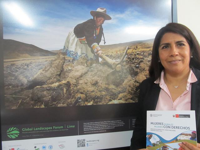 """María Elena Rojas, representante en Perú de la FAO, en su oficina en Lima, ante una imagen de una mujer andina arando la tierra y con un documento en sus manos, cuyo título es toda una declaración de intenciones: """"Mujeres rurales, mujeres con derechos"""". Crédito: Mariela Jara/IPS"""