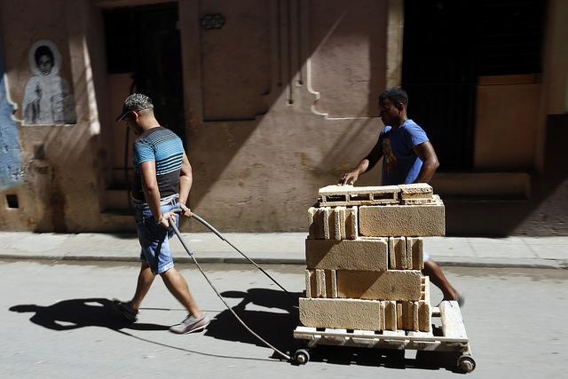 Dos jóvenes transportan bloques de construcción artesanal destinados a la ampliación de una vivienda en La Habana Vieja, en Cuba. Crédito: Jorge Luis Baños/IPS