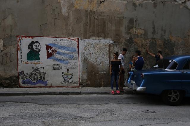 Un grupo de jóvenes cubanos conversa cerca un grafiti donde aparece la imagen del expresidente Fidel Castro y su concepto de Revolución, en el centro de La Habana. Crédito: Jorge Luis Baños/IPS