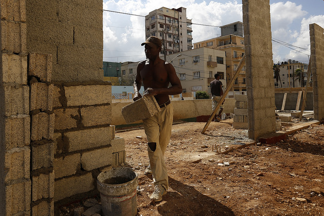 Un trabajador coloca bloques de construcción elaborados artesanalmente en la construcción de parte de una vivienda vecina a una zona afectada por los efectos del huracán Irma, en el barrio del Vedado, en la capital de Cuba. Crédito: Jorge Luis Baños/IPS