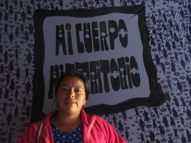 """Fanny Kaekat, lideresa indígena del pueblo shuar arutam, lleva una vida defendiendo los territorios de sus comunidades en el sureste de Ecuador de la amenaza de la explotación minera. Posa en el 14 Encuentro Feminista Latinoamericano, en Montevideo, delante de un cartel que reza: """"mi cuerpo, mi territorio"""", un lema de las defensoras de derechos. Crédito: Mariela Jara/IPS"""