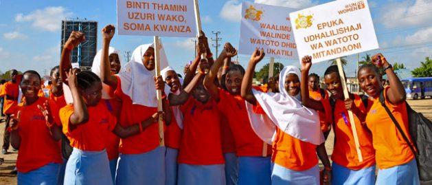 """Niñas vestidas con el color naranja de la campaña del activismo para erradicar la violencia hacia las mujeres, se manifiestan en Dar es Salaam, en Tanzania. Un letrero dice: """"Absténgase de usar lenguaje ofensivo para mujeres y niñas"""". Crédito: Deepika Nath/ONU Mujeres"""